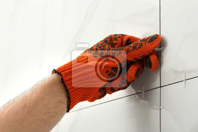 Man putting plastic cross into joint between ceramic tiles on wall, closeup. Building and renovation works