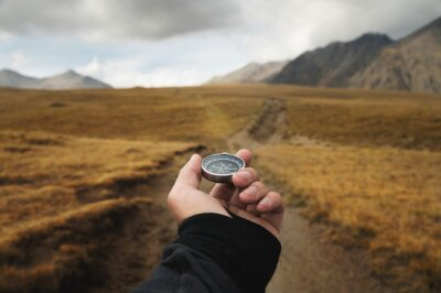 Naklejka Man's hand holding a magnetic compass first-person view against the background of a high-altitude path and mountains