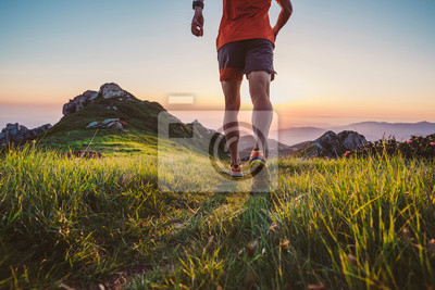 Naklejka Man trail running on a mountain at the dask