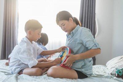 matka i chłopiec grać drewniane zabawki na łóżku w home.happy dzień rodziny