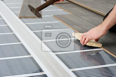 Mężczyzna instalacji podłogę laminowaną na podczerwień st. ogrzewania węglowego