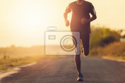 Naklejka Mężczyzna z biegaczem na ulicy biegnie do ćwiczeń.