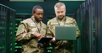 Naklejka Mixed-races army men in camouflage talking and discussing some secret information in server room. African American and Caucasian male co-workers of military forces with tablet and laptop computer.