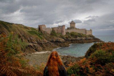 Naklejka Młoda biała kobieta rasy białej o długich rudych włosach stoi na tle słynnego średniowiecznego zamku la Latte twierdzy jesienią podczas burzy na Morzu Celtyckim w Normandii we Francji