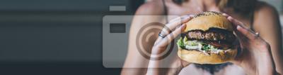 Naklejka Młoda dziewczyna trzyma w rękach kobiet fast food burger, amerykański niezdrowe kalorie posiłek na niebieskim tle, makieta z miejsca kopiowania dla wiadomości tekstowej, głodnych ludzi z grilla hambur
