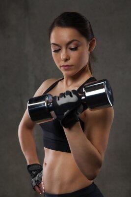 Naklejka Młoda kobieta wyginanie mięśni z hantlami w siłowni