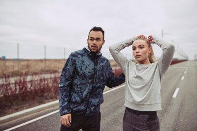 Naklejka Młoda para w sportowej stojącej razem na wiejskiej drodze