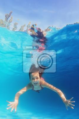 Młoda szczęśliwa uśmiechnięta dziecko pływanie pod wodą w niebieskim basen