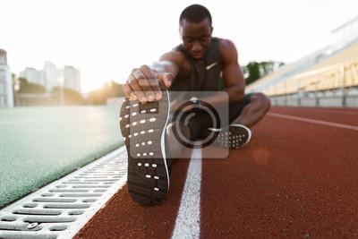 Naklejka Młode skoncentrowane afrykańskie męskie lekkoatletyka rozciągające nogi