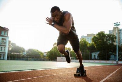 Naklejka Młody biegacz afrykański biegnie na torze wyścigowym