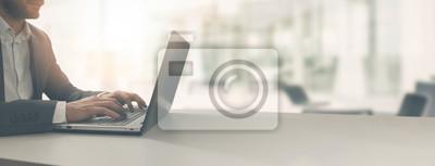 Naklejka młody biznesmen pracuje na laptopie w nowoczesnym biurze jasny coworking. kopia przestrzeń