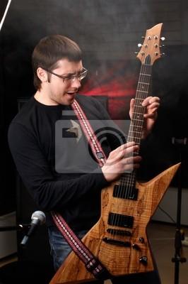 Młody mężczyzna gra na gitarze w nauce