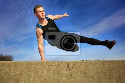 Młody mężczyzna przeskakując mur na torze przeszkód