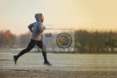 Naklejka Młody mężczyzna sportowiec uruchomiony w parku w zimny jesienny poranek
