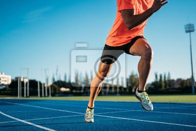 Naklejka Młody mężczyzna sportowiec zaczyna biegać w pozycji początkowej w wyścigu. Rozpocznij krok