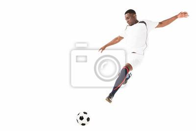 młody piłkarz african american kopiąc piłkę w skok na białym tle