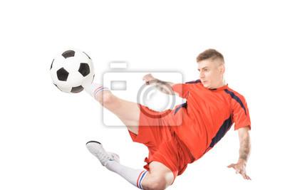 młody piłkarz kopiąc piłkę w skok na białym tle