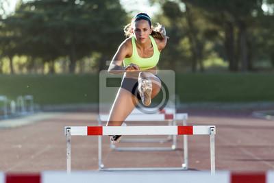 Naklejka Młody sportowiec skoków przez przeszkody podczas treningu wyścigowym trac