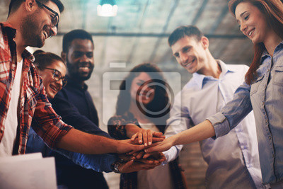 Naklejka Młodzi ludzie pokazujący ducha zespołu koncentrują się na rękach