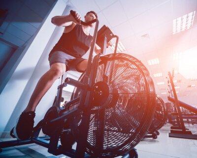 Naklejka Młodzi mężczyźni z muskularnym ciałem za pomocą roweru powietrznego do treningu cardio w siłowni do ćwiczeń krzyżowych.
