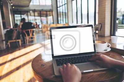Naklejka Mockup wizerunek kobiety za pomocą laptopa z pustym białym ekranem na drewnianym stole w nowoczesnej kawiarni na poddaszu