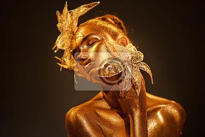 Moda modela kobieta w kolorowy jaskrawy złoty błyska pozować z fantazja kwiatem. Portret piękna dziewczyna z rozjarzonym makeup