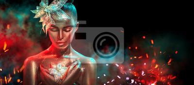 Moda modela kobieta w kolorowych jaskrawych złotych błyskotaniach i neonowych światłach pozuje z fantazja kwiatem. Portret piękna dziewczyna z rozjarzonym makeup