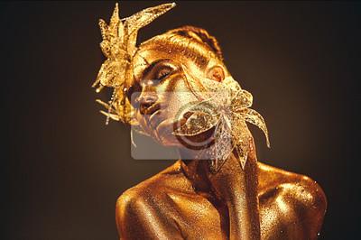 Moda złota modelka z jasnym złotem błyszczy na skórze pozując, kwiat fantazji. Portret pięknej dziewczyny z świecące makijaż. Błyszcząca świecąca skóra, biżuteria