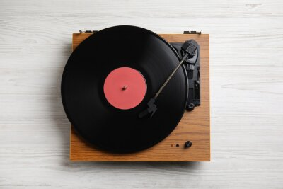 Naklejka Modern vinyl record player with disc on white wooden background, top view