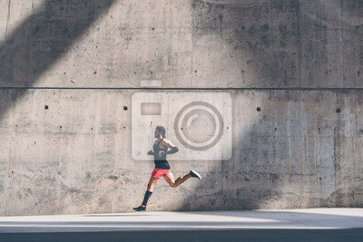 Naklejka Muscular Male athlete sprinter running fast,exercising outdoors,jogging outside against gray concret background with copy space area for text message or ad content.Side view,full length