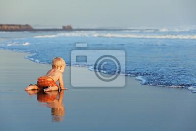 Na zachód słońca, piaszczystej plaży dziecko czołganie się do morza do pływania