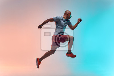 Naklejka New champion. Full length of young african man in sports clothing jumping against colorful background