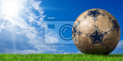 Niebieski i brązowy Piłka nożna (Piłka nożna) z zielona trawa i błękitne niebo z chmurami i promieni słonecznych