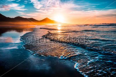 Naklejka Niesamowity zachód słońca na plaży z niekończącym się horyzontem i samotnymi postaciami w oddali oraz obsługiwanymitmi spienionymi falami. Wulkaniczne wzgórza w tle.
