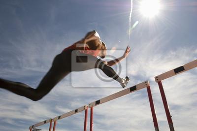Naklejka Niski kąt widzenia mężczyzny sportowca skoki przeszkodę na tle nieba