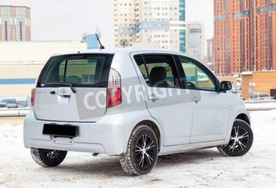 Naklejka Novosibirsk, Russia - 02.17.2020: Used silver Toyota Passo with an engine of 1.3 liters rear view on the car snow parking after preparing for sale