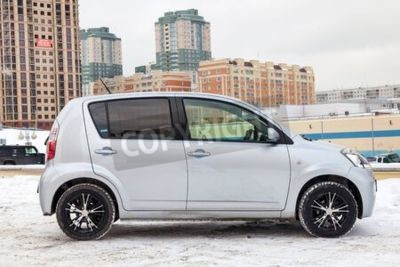 Naklejka Novosibirsk, Russia - 02.17.2020: Used silver Toyota Passo with an engine of 1.3 liters side view on the car snow parking after preparing for sale