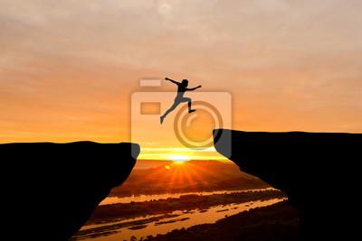 Naklejka Odwaga człowiek skacząc nad urwiska na tle słońca, pojęcie pomysł na biznes