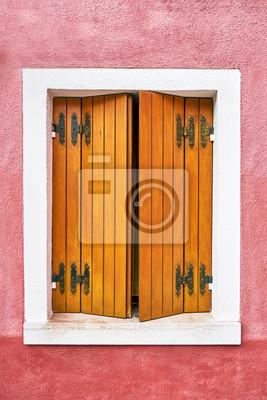 Okno z ładne drewniane okiennice na czerwonej ścianie. Włochy, Wenecja, Burano