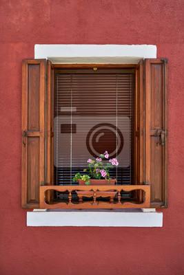 Okno z stare drewniane okiennice i różowe kwiaty w doniczce. Włochy, Wenecja, Burano