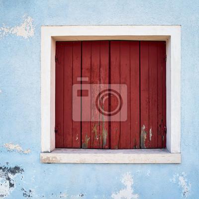 Okno z zamkniętą czerwoną żaluzją na błękit ścianie. Włochy, Wenecja, wyspa Burano.