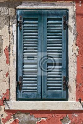Okno z zamkniętą starą zieleni zieleni żaluzją na czerwieni ścianie. Włochy, Wenecja, wyspa Burano.