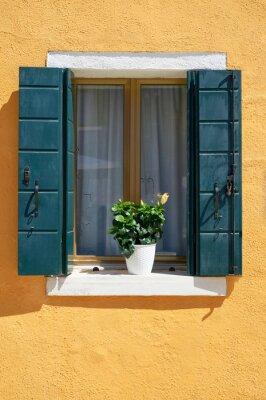 Okno z zielonymi okiennicami i żółtymi kwiatami w doniczce. Tradycyjne kolorowe ściany i okna. Włochy, Wenecja, Burano