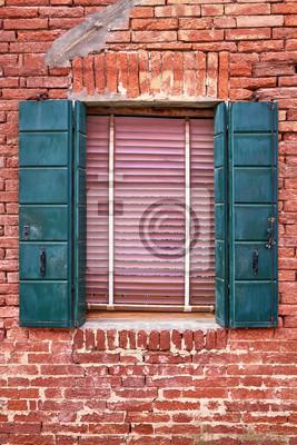 Okno z zielonymi żaluzjami na czerwonym ściana z cegieł domy. Włochy, Wenecja, Burano.