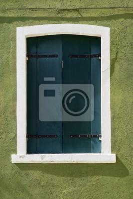 Okno z zielonymi żaluzjami na zieleni ścianie domy. Włochy, Wenecja, Burano.