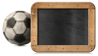 Old leather soccer ball and an empty blackboard with copy space isolated on white background