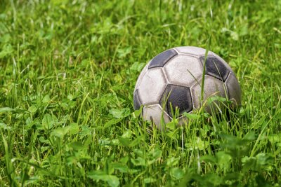 Old leather soccer ball on green grass with copy space, football sport concept