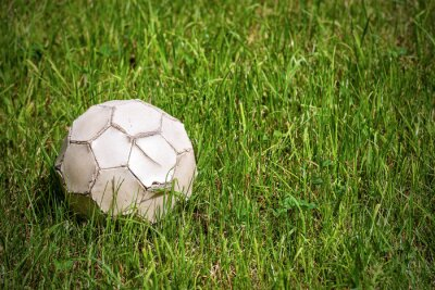 Old white leather soccer ball on green grass with copy space, football sport concept