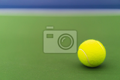 one new tennis ball on blue and green hard court with copy space on left