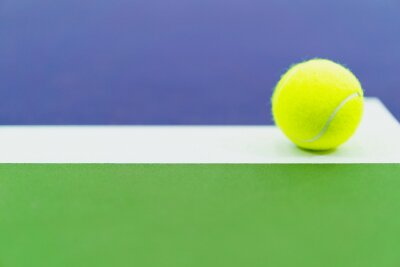 one new tennis ball on white line in blue and green hard court, copy space on left